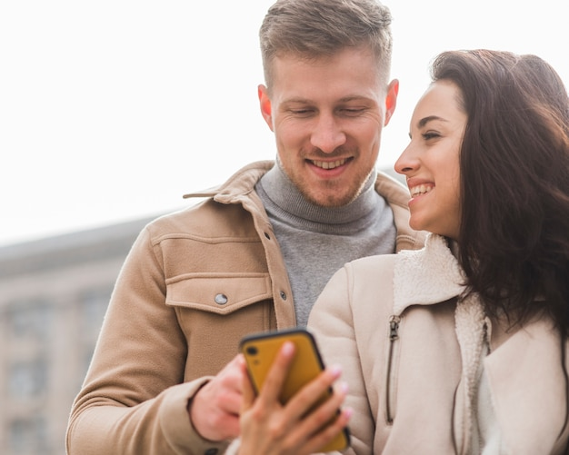 Smiley couple looking at smartphone