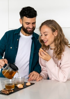 Smiley couple making tea at home together