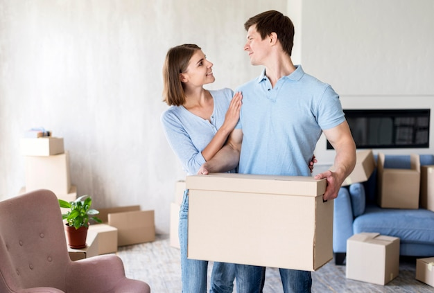 Smiley couple on moving out day holding box