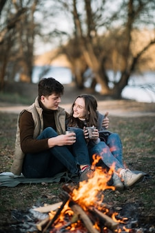 Smiley couple near campfire