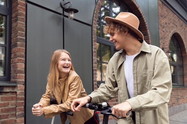 Coppia di smiley all'aperto in città con scooter elettrici