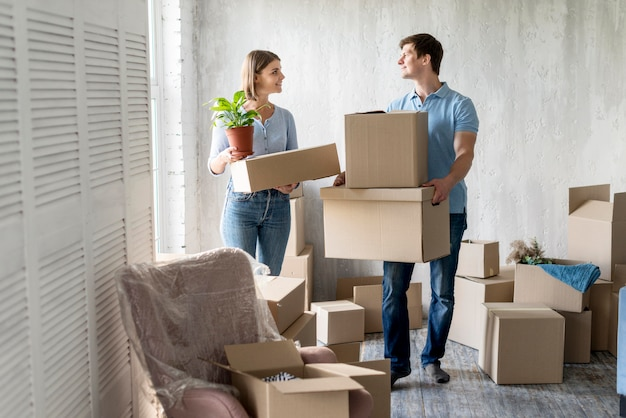 Smiley couple packing together to move house