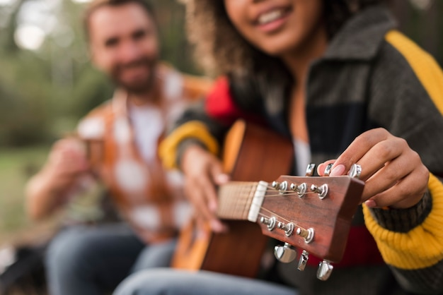 Smiley couple playing guitar outdoors while camping