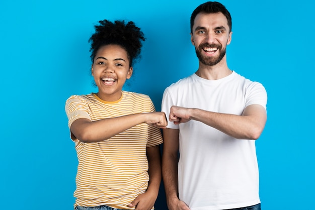 Smiley couple posing and fist bumping