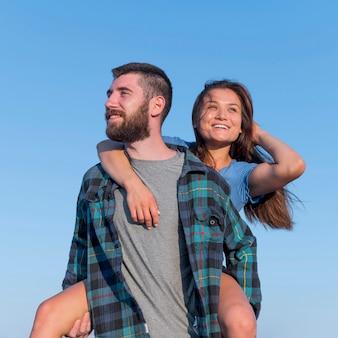 Смайлик пара позирует вместе на открытом воздухе