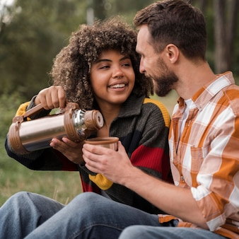 Smiley couple spending time together while camping