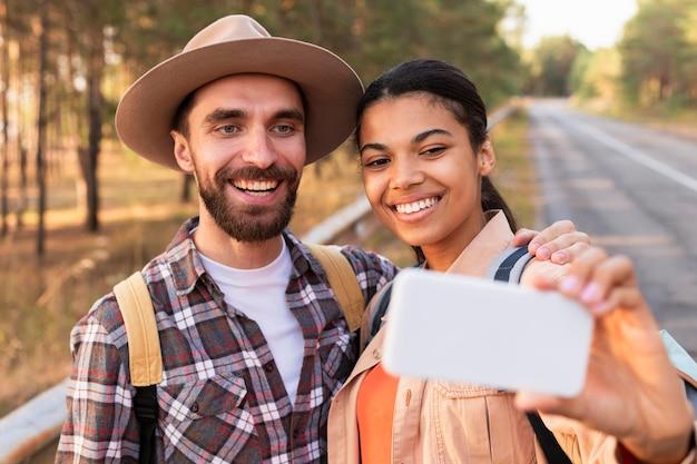 Смайлик пара, делающая селфи со смартфоном
