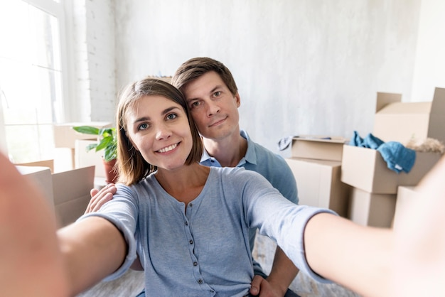 Smiley couple taking a selfie while packing to move out
