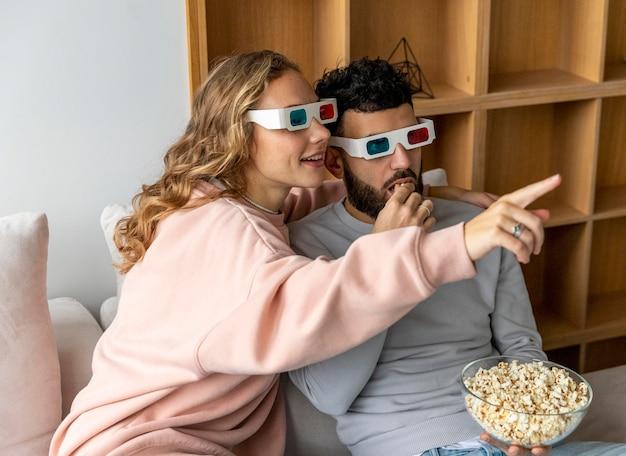 3 차원 안경으로 집에서 영화를보고 팝콘을 먹는 웃는 커플