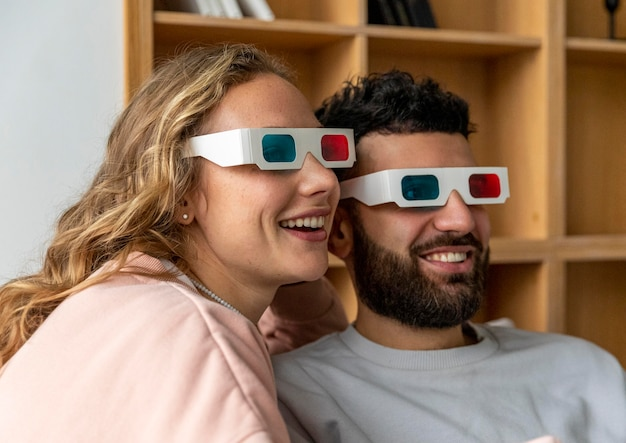 Smiley couple watching movie at home with three-dimensional glasses