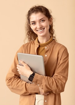 Smiley curly haired lady holding laptop