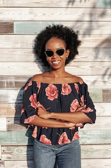 Smiley curly haired woman wearing sunglasses