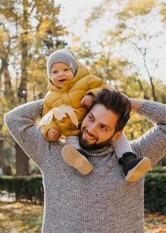 屋外で赤ちゃんと一緒にスマイリーのお父さん