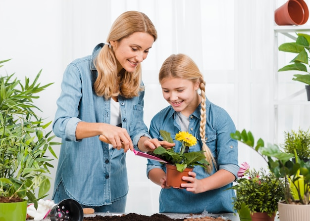 Smiley daughter and daughter caring flowers