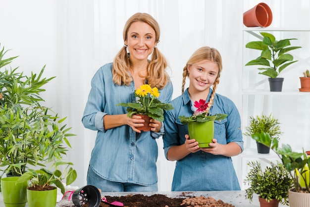 Smiley daughter and mom holding flowers pot