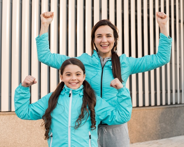 Smiley daughter and mom showing muscles