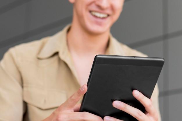 Smiley defocused man looking at tablet outdoors