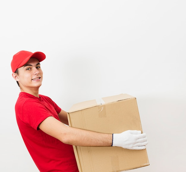Smiley delivery man carrying package