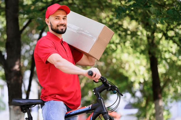 Smiley delivery man carrying parcel on a bike