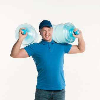 Smiley delivery man carrying water bottles on shoulders