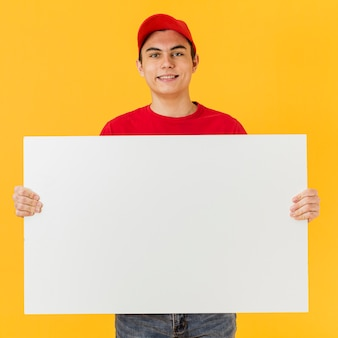 Smiley delivery man holding blank paper sheet
