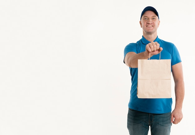 Smiley delivery man holding paper bag with copy space