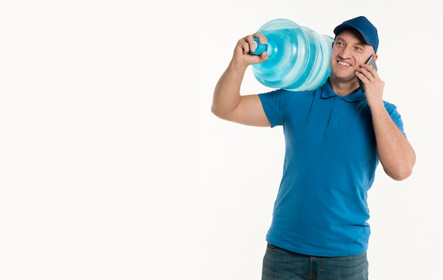 Smiley delivery man holding smartphone and carrying water bottle