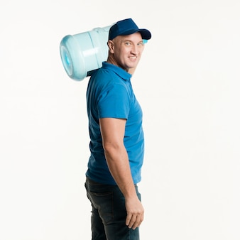 Smiley delivery man posing with water bottle