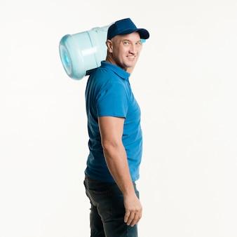 Uomo di consegna di smiley che propone con la bottiglia di acqua