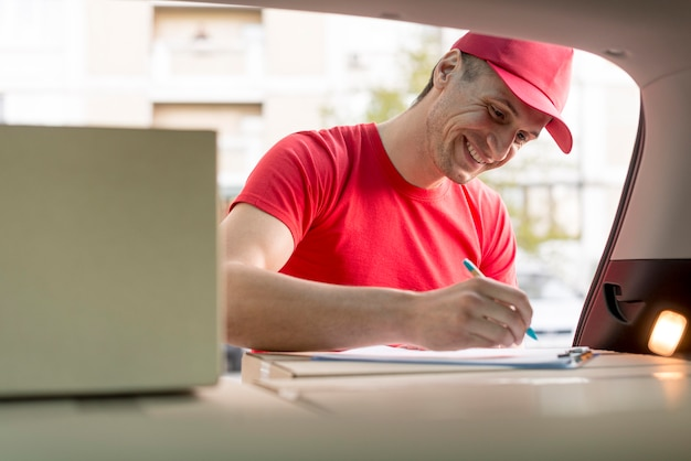 Smiley delivery man signing document