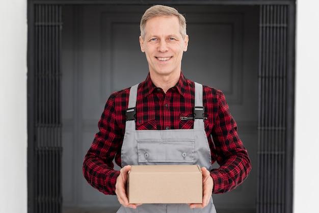 Uomo di consegna di smiley con pacchetto