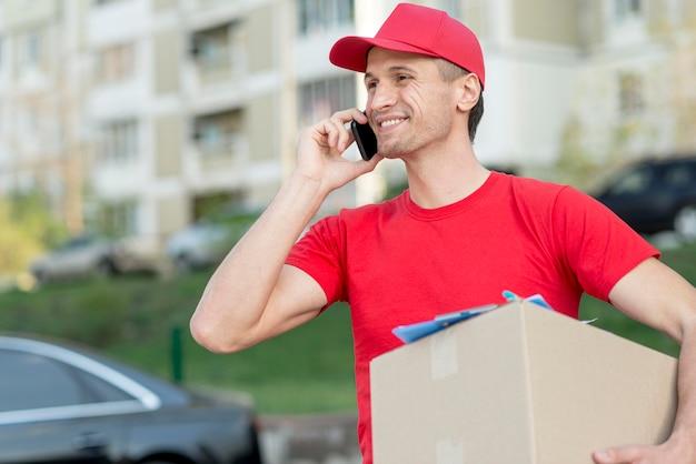 Uomo di consegna di smiley con smartphone