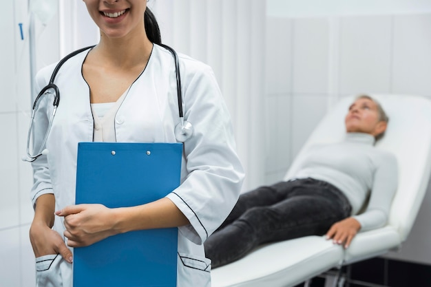 Smiley doctor next to blurry patient