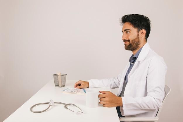 Medico di sorriso che beve il caffè alla sua scrivania