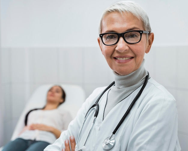 Смайлик врач позирует рядом с пациентом