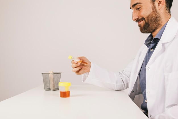 Smiley doctor with an urine test at his desk