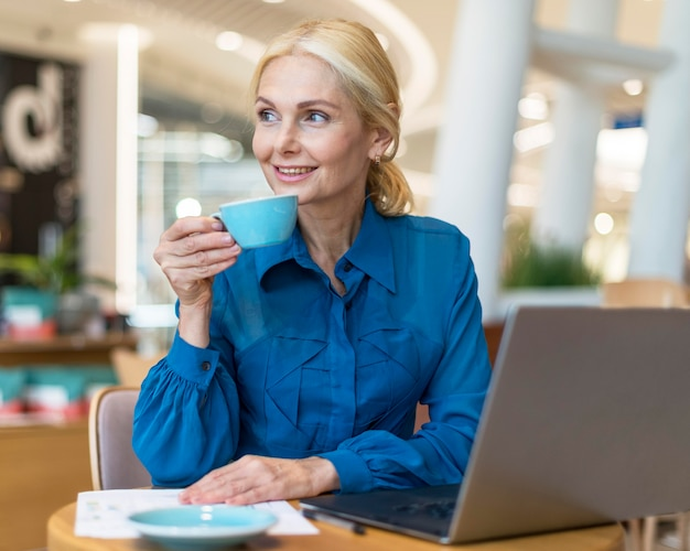 Smiley elder business woman enjoying cup of coffee while working