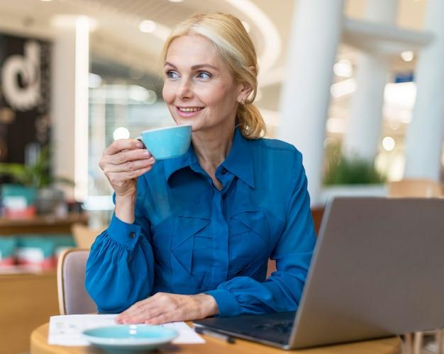 Donna anziana di affari di smiley che gode della tazza di caffè mentre lavora