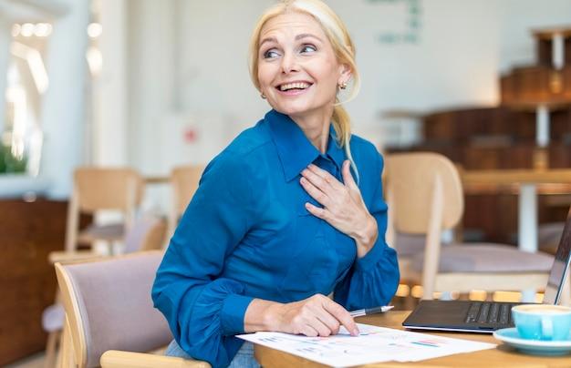 Donna anziana di affari di smiley fuori che lavora al computer portatile