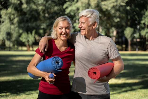 Smiley elder couple outdoors with yoga mats and water bottle