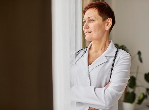 Medico femminile del centro di recupero covid dell'anziano di smiley che osserva attraverso la finestra