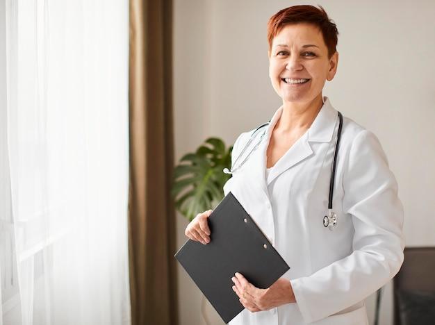 Medico femminile del centro di recupero covid dell'anziano di smiley con la lavagna per appunti e lo stetoscopio