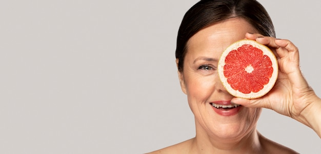 Smiley elder woman covering her eye with half of grapefruit