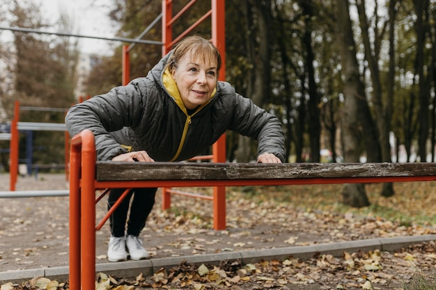 Smiley elder woman doing push-ups outdoors