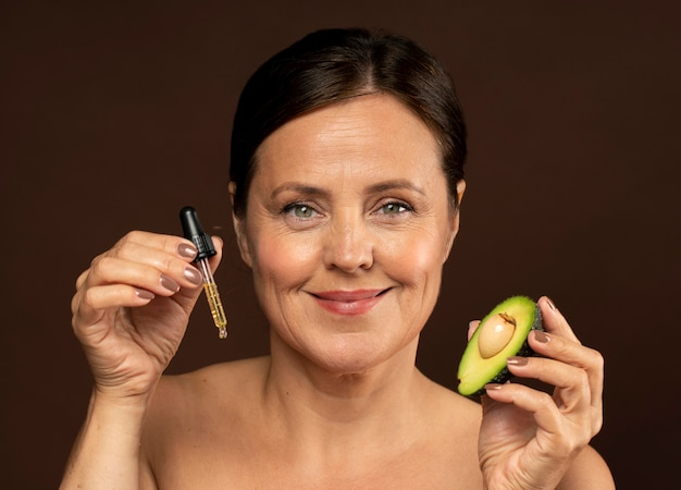Smiley elder woman holding half of an avocado with serum