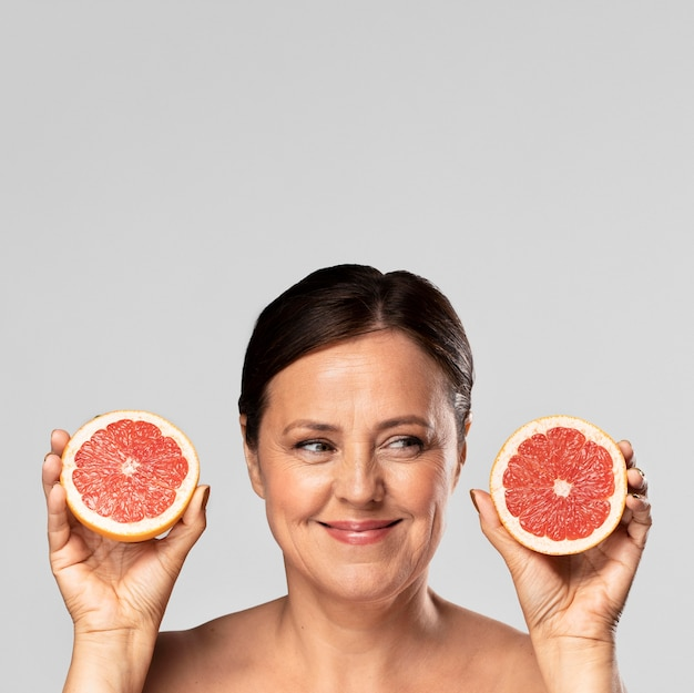 Smiley elder woman holding half of grapefruit in each hand