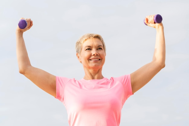 운동하는 동안 무게를 들고 웃는 노인 여성