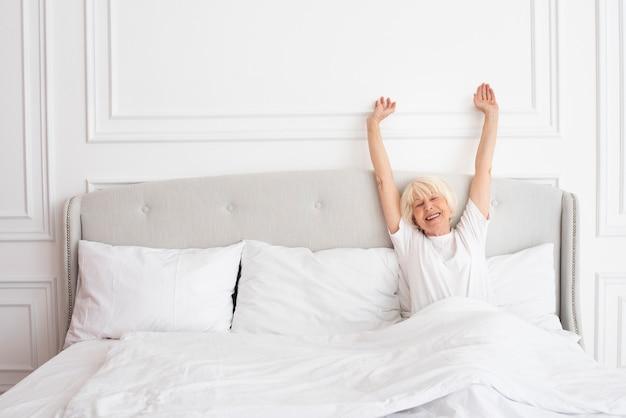침실에 누워 웃는 노인 여성