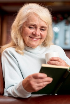 Smiley elder woman reading