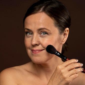 Смайлик старшая женщина, используя кисть для макияжа на лице